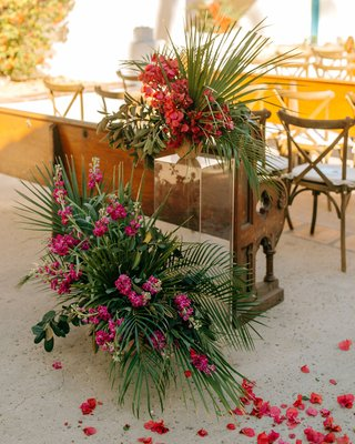 wedding ceremony entrance decor pink bougainvillea and green palm wood pew petals on floor