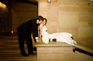 man-kissing-shoulder-of-woman-in-wedding-dress