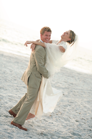 groom-in-khaki-suit-picks-up-bride-in-lace-wedding-dress-on-beach