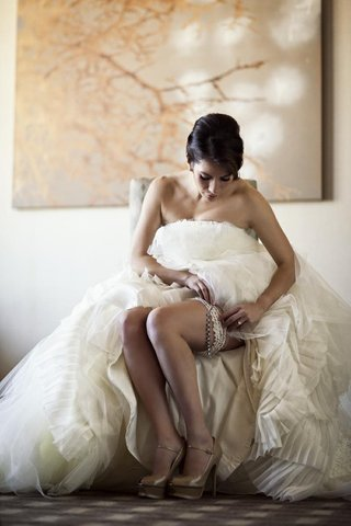 woman-in-bridal-gown-wearing-lace-garter-and-heels