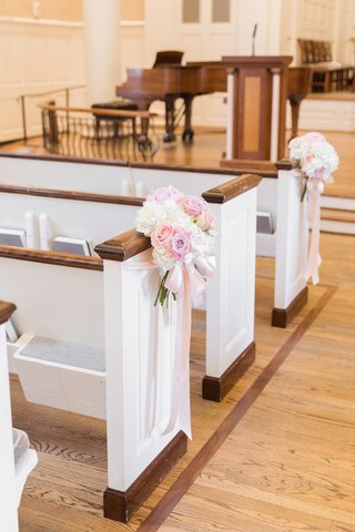 ivory-and-pink-flowers-displayed-on-pews-at-church-ceremony