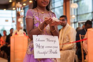 indian-flower-girl-in-traditional-lavender-dress-with-sign-for-groom