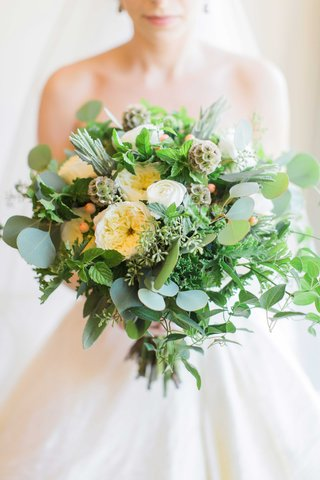 bride-holding-bouquet-with-eucalyptus-leaves-white-garden-roses-scabiosa-pods-rosemary-thyme