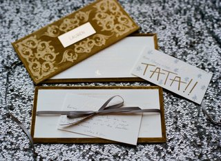 gold-velvet-box-on-sequin-tablecloth-with-handwritten-note-to-guests