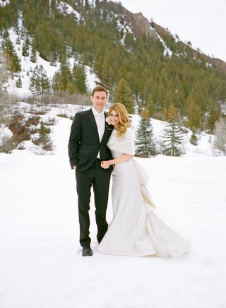 couple-in-wedding-attire-standing-in-snow