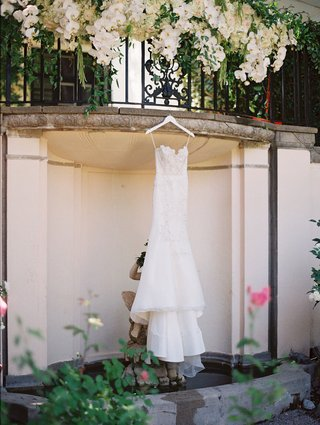 a-brides-trumpet-gown-with-scalloped-neckline-suspended-from-balcony-over-pond