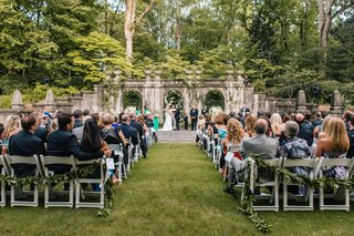 atlanta-history-center-wedding-ceremony-on-grass-lawn-stone-walls-greenery-green-garlands-on-chairs