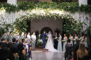 ebell-long-beach-wedding-ceremony-with-orchids-and-greenery-from-balcony-with-bridal-party-under
