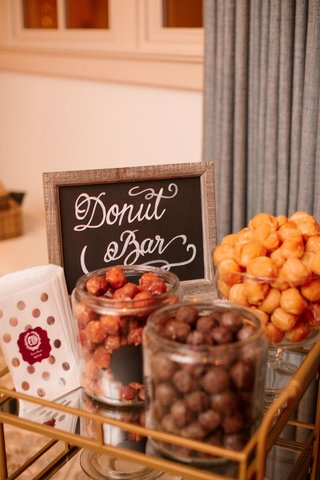 wedding-reception-bar-cart-with-donut-holes-in-glass-jars-and-take-home-bags-with-monogram
