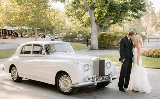 bride-in-a-strapless-hayley-paige-dress-kisses-groom-in-black-tuxedo-by-vintage-white-rolls-royce