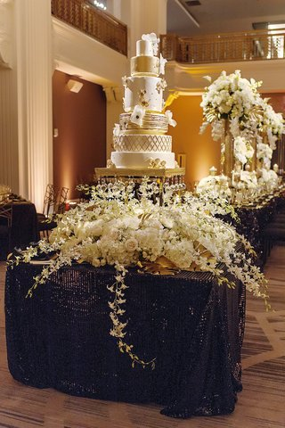 six-tier-cake-with-painted-gold-leaf-and-handmade-sugar-flowers-crystals-on-stand-floral-display