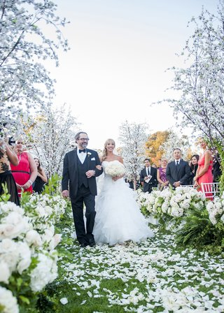bride-in-full-ball-gown-walking-down-the-aisle-with-her-dad-outdoor-wedding-with-flower-petals
