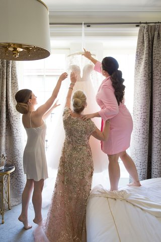 mother-of-bride-in-sparkle-dress-helping-bride-in-slip-and-other-daughter-in-pink-robe-with-dress