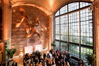 wedding-cocktail-hour-guests-in-lobby-of-venue-tall-glass-window-new-york-city-venue