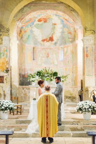 bride-and-groom-at-stone-altar-italy-destination-wedding-fresco-paintings-on-walls-abbey-venue