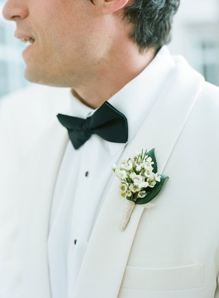 groomsman-in-white-tuxedo-jacket-with-lily-of-the-valley-boutonniere-black-bow-tie