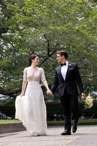 bride-in-lace-v-neck-carolina-herrera-groom-in-ralph-lauren-holds-hands-and-bouquet