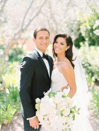 bride-in-strapless-monique-lhuillier-wedding-dress-blush-botanicals-with-large-white-bouquet-veil