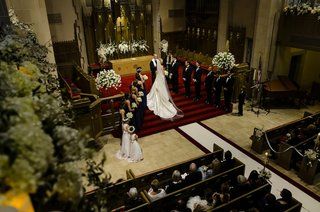 bride-and-groom-at-altar-steps-of-classic-church-with-white-flowers