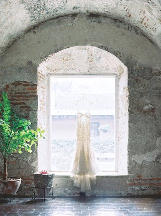 wedding-dress-hanging-in-window-of-old-building-in-antigua-guatemala-liancarlo-spanish-lace
