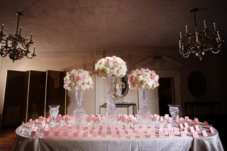 pink-escort-cards-on-white-oval-table-with-tablecloth-and-tall-arrangements-with-crystal-vases