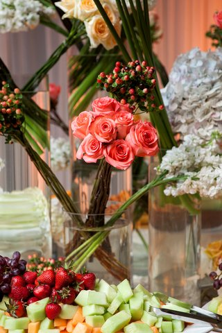 wedding-reception-with-roses-and-hydrangeas-in-cylinder-vases-decorating-a-fruit-table