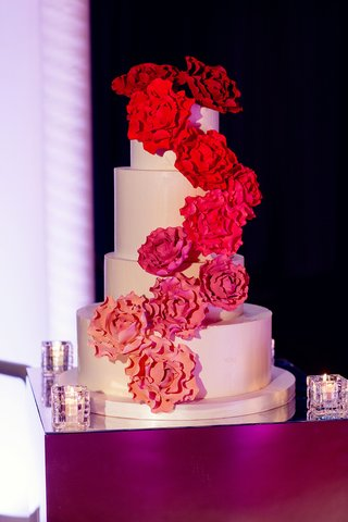 white-cake-with-sugar-flowers-cascading-down-side-in-shades-of-pink
