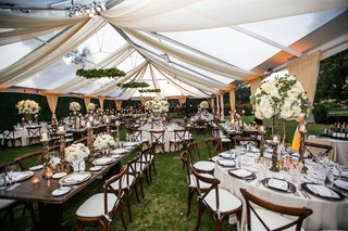 wedding-reception-alabaster-drapery-tent-venue-wood-table-round-tables-white-centerpiece