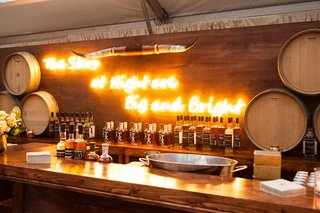 neon-sign-behind-bar-with-rustic-horns-and-barrels