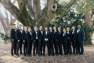 large-group-of-groomsmen-in-tuxedos-at-black-tie-wedding-posed-outdoors-under-tree
