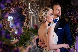 bride-with-wavy-blonde-hair-in-updo-open-back-and-beaded-straps-groom-in-navy-tuxedo