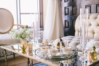 wedding-reception-with-white-and-gold-coffee-servide-on-a-mirror-top-table-with-golden-candleholders