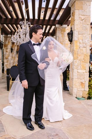 bride-in-riki-dalal-couture-with-long-blusher-veil-stands-with-her-father-in-a-tux