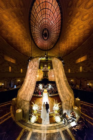 bride-in-julie-vino-wedding-dress-walking-down-aisle-with-dad-tall-ceiling-gotham-hall-drapes-lights