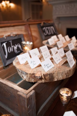 wedding-reception-with-place-cards-displayed-on-wood-slabs-on-top-of-distressed-wood-crates
