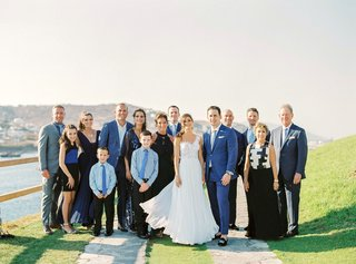bride-in-one-shoulder-mira-zwillinger-wedding-dress-groom-in-blue-suit-with-family-mykonos-wedding