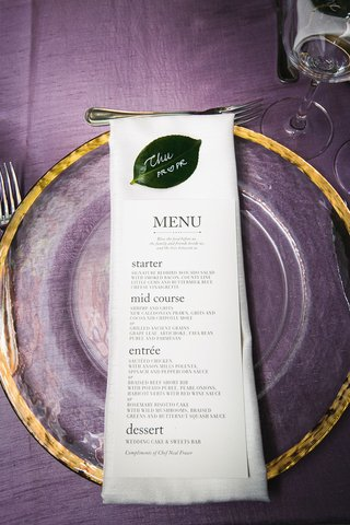 wedding-menu-on-top-of-linen-napkin-clear-gold-charger-green-leaf-place-card-purple-linens