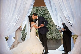bride-in-off-shoulder-wedding-dress-kisses-groom-at-wedding-under-draped-chuppah-white-flowers
