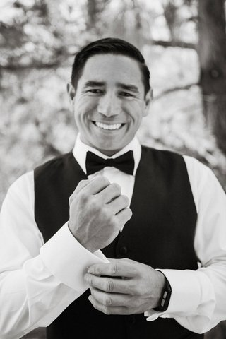 black-and-white-photo-of-groom-smiling-with-black-vest-bow-tie-adjusting-cuff-links