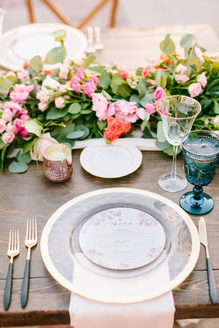 wood-table-gold-black-flatware-gold-charger-plate-blush-napkin-blue-goblet-pink-orange-flowers-green