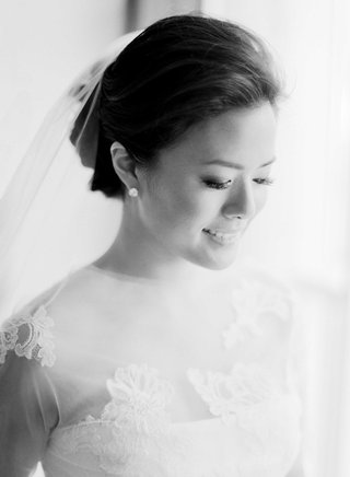 black-and-white-photo-of-bride-with-stud-earrings-veil-on-updo-and-lace-vera-wang-wedding-dress