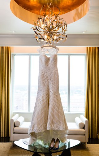 wedding-dress-with-keyhole-back-hanging-from-odern-chandelier-artwork-in-hotel-room-skyline-wedding