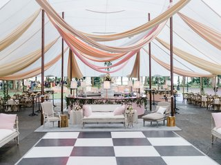 wedding-reception-tent-checkerboard-dance-floor-lounge-furniture-wood-chairs-linen-tables-bar