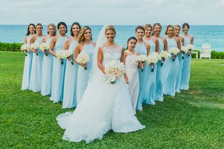 bride-in-isabelle-armstrong-with-bridesmaids-in-bright-blue-amsale-gowns-posed-in-v-forma