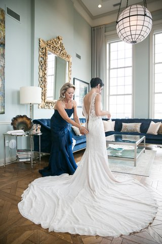 mother-of-the-bride-in-blue-dress-zips-up-bride-in-rivini-wedding-dress