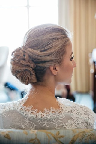 bride-in-white-lace-robe-with-hair-pulled-back-into-updo-with-braid