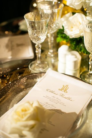 wedding reception white gold decor design gold monogram with guest name written on top of menu