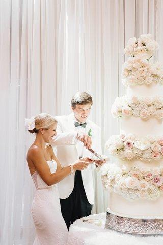 bride-in-inbal-dror-wedding-dress-and-groom-in-white-tuxedo-jacket-cut-into-wedding-cake-flowers