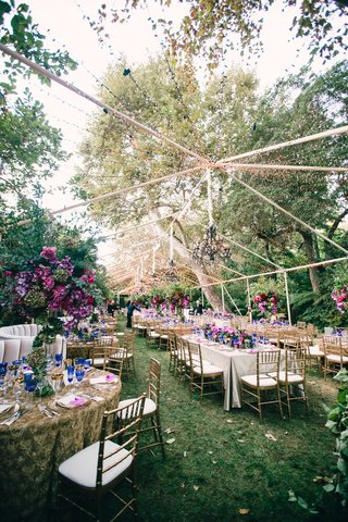 beautiful-clear-top-tent-at-wedding-reception-with-chandelier-string-light-and-purple-flowers