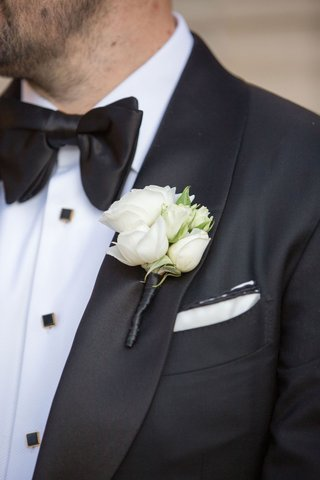 groom in tuxedo white pocket square with gold black buttons bow tie and white flower boutonniere rose buds
